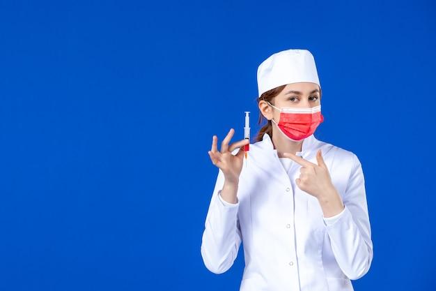 Jovem enfermeira de vista frontal em um terno médico com máscara vermelha e injeção nas mãos na parede azul