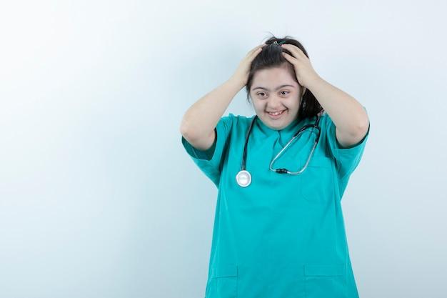 Jovem enfermeira feminina com estetoscópio posando contra uma parede branca.