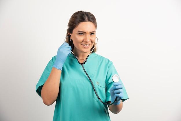 Jovem enfermeira feminina sorridente posando com estetoscópio.