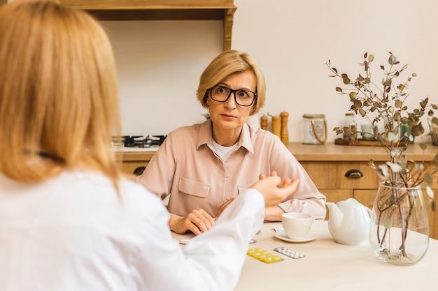Jovem enfermeira fornece atendimento médico ajuda a apoiar a mulher madura sênior na visita médica domiciliar, senhora cuidadora dá empatia encoraja o paciente aposentado na cozinha.