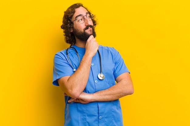 Jovem enfermeira homem pensando contra parede amarela