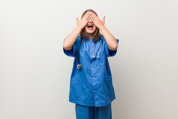 Jovem enfermeira mulher contra uma parede branca cobre os olhos com as mãos, sorri amplamente esperando por uma surpresa.