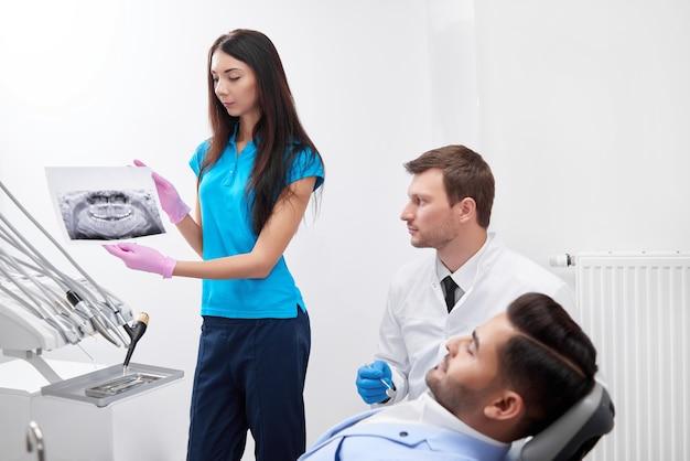 Jovem enfermeira segurando um raio-x de uma mandíbula ajudando um homem adulto