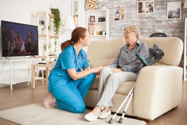 Jovem enfermeira vestindo uniforme azul, falando com uma mulher sênior em uma casa de repouso.