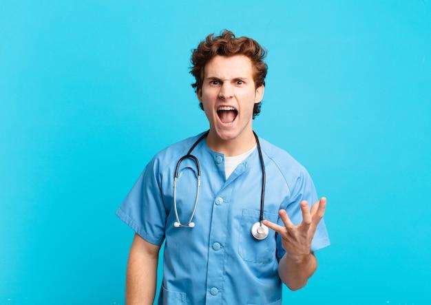 Jovem enfermeiro parecendo zangado, irritado e frustrado gritando wtf ou o que há de errado com você