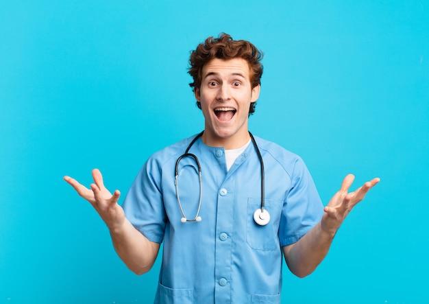 Jovem enfermeiro sentindo-se feliz, animado, surpreso ou chocado, sorrindo e surpreso com algo inacreditável