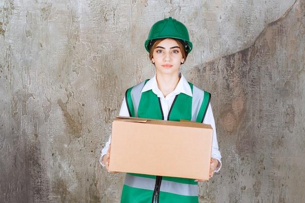 Jovem engenheira com colete verde e capacete segurando uma caixa de papel