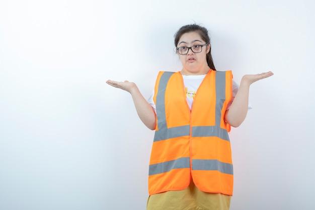 Jovem engenheira de óculos segurando um espaço aberto na parede branca