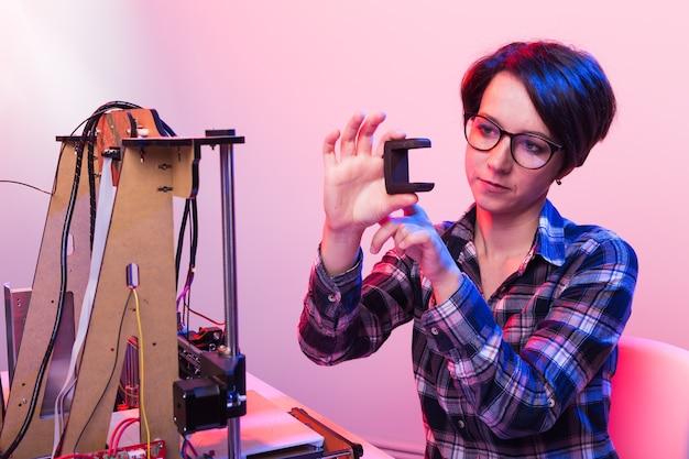 Jovem engenheira designer usando uma impressora no laboratório e estudando um protótipo de produto, conceito de tecnologia e inovação.