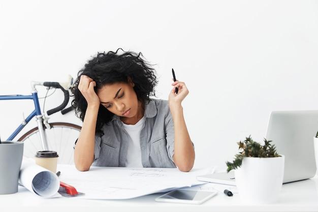 Jovem engenheira infeliz trabalhando em casa em um grande projeto