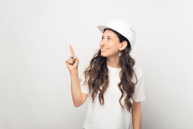 Jovem engenheira ou arquiteta está apontando para cima enquanto usava um capacete branco.