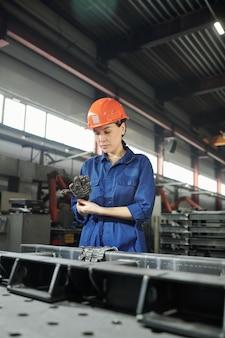 Jovem engenheira séria em vestuário de trabalho, calçando luvas antes do trabalho, com enormes detalhes de ferro de máquina industrial