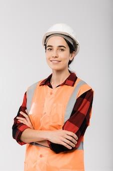 Jovem engenheira sorridente com capacete e jaqueta laranja, cruzando os braços no peito em frente à câmera