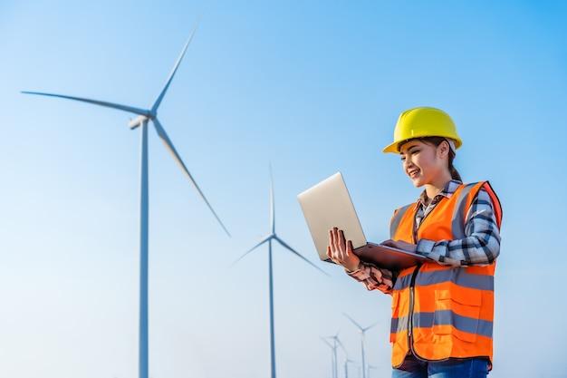 Jovem engenheira trabalhando com um laptop contra uma fazenda de turbinas eólicas