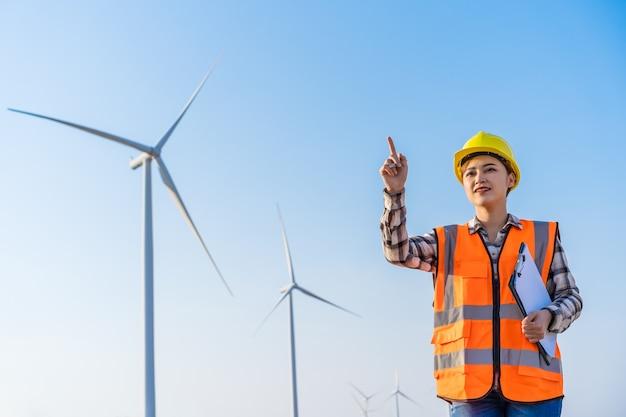 Jovem engenheira trabalhando contra uma fazenda de turbinas eólicas
