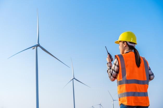 Jovem engenheira usando walkie-talkie para verificar o sistema em relação ao parque de turbinas eólicas