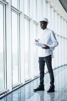 Jovem engenheiro afro-americano com estampas azuis na frente de janelas panorâmicas no escritório