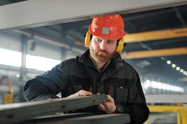 Jovem engenheiro barbudo em capacete protetor e fones de ouvido processando um dos detalhes de ferro da máquina industrial