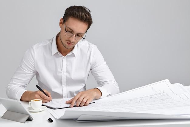 Jovem engenheiro-chefe europeu barbudo talentoso, usando óculos redondos e camisa formal branca, sentado no local de trabalho