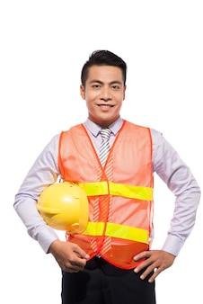 Jovem engenheiro com capacete amarelo é isolado no fundo branco.