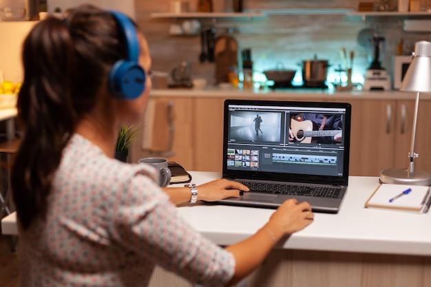 Jovem engenheiro de som trabalhando em imagens de vídeo durante a pós-produção. criador de conteúdo em casa trabalhando na montagem de filme usando software moderno para edição tarde da noite.