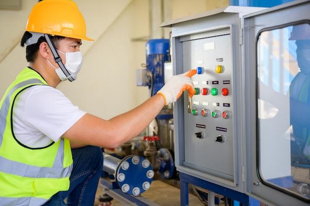 Jovem engenheiro elétrico usando uma máscara inspecione o gabinete de controle elétrico e o sistema de controle elétrico no prédio e execute verificações diárias por um técnico de serviço na fábrica