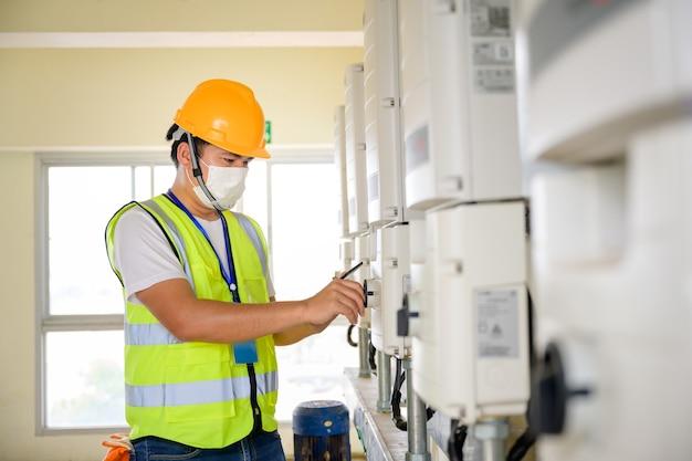 Jovem engenheiro elétrico usando uma máscara inspecione o painel de controle fotovoltaico e o sistema de controle elétrico interno por um técnico de sistema fotovoltaico.