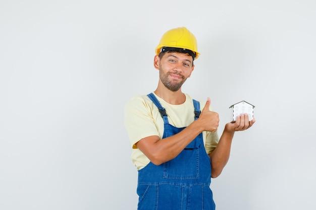 Jovem engenheiro em uniforme segurando o modelo da casa com o polegar para cima e olhando alegre, vista frontal.