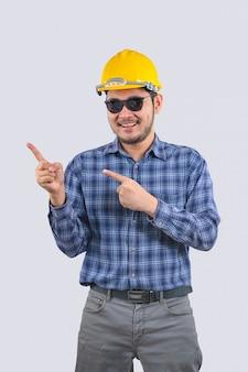 Jovem engenheiro homem asiático vestindo camisas listradas de manga longa está apontando para um espaço vazio à direita