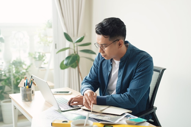Jovem engenheiro. homem ocupado e bem-sucedido desenhando algo enquanto trabalhava no escritório