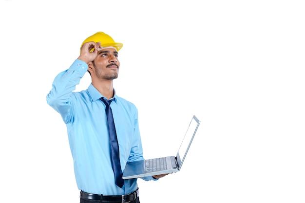 Jovem engenheiro indiano de uniforme e usando laptop em fundo branco.