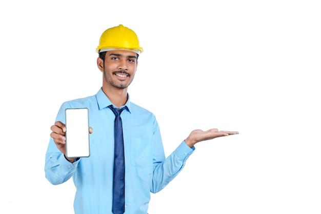 Jovem engenheiro indiano ou trabalhador da construção civil mostrando a tela do smartphone.
