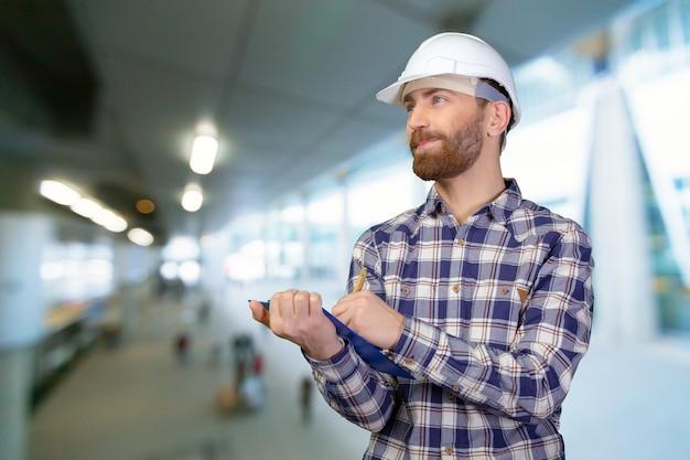 Jovem engenheiro masculino com capacete segurando plantas