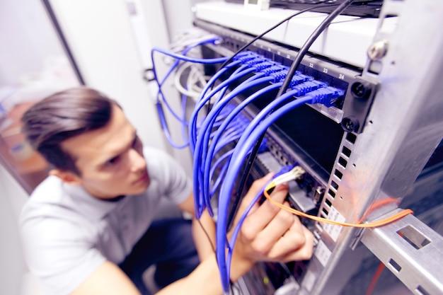 Jovem engenheiro na sala de servidores de rede conectando fios