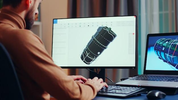 Jovem engenheiro, olhando de perto para o projeto da turbina, enquanto trabalhava em seu escritório em casa à noite.