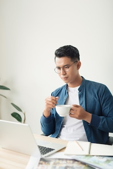 Jovem engenheiro ou contador com caneta e xícara de café, fazendo cálculos e anotações em um caderno no escritório