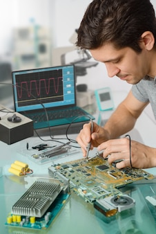 Jovem engenheiro ou técnico masculino repara equipamentos eletrônicos em instalações de pesquisa