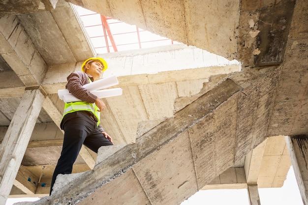 Jovem engenheiro profissional trabalhador em capacete protetor e papel de plantas disponíveis no local de construção do edifício da casa