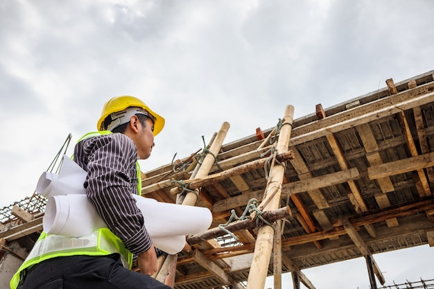 Jovem engenheiro profissional trabalhador em capacete protetor e papel de plantas disponíveis trabalhando na escada no local de construção do edifício da casa