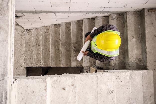 Jovem engenheiro profissional trabalhador em capacete protetor e papel de plantas em mãos no local de construção do edifício