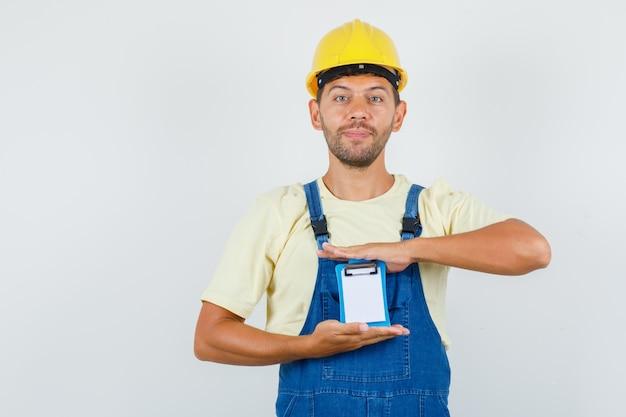 Jovem engenheiro segurando mini prancheta de uniforme e olhando alegre, vista frontal.