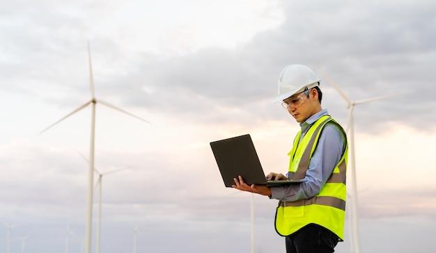 Jovem engenheiro trabalhando com um laptop contra uma fazenda de turbinas eólicas
