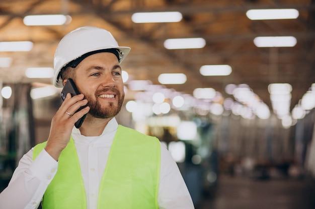 Jovem engenheiro trabalhando na fábrica, fazendo pedidos pelo telefone