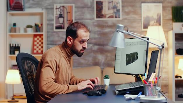 Jovem engenheiro trabalhando tarde da noite em seu escritório em casa para terminar a turbina moderna.
