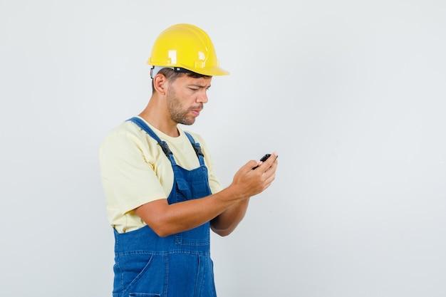 Jovem engenheiro usando telefone celular de uniforme e parecendo preocupado, vista frontal.