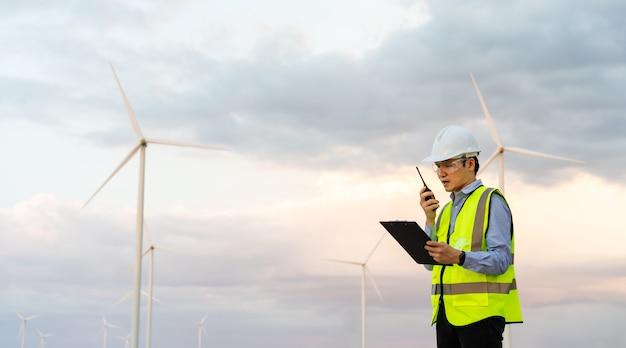 Jovem engenheiro usando walkie-talkie e lendo a prancheta para verificar o sistema em um parque de turbinas eólicas