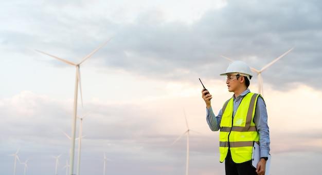 Jovem engenheiro usando walkie-talkie para verificar o sistema em relação ao parque de turbinas eólicas
