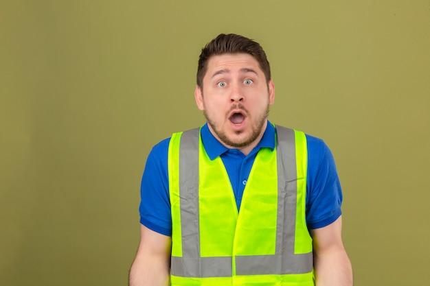 Jovem engenheiro vestindo colete de construção, parecendo fascinado com a surpresa de descrença e expressão de espanto em pé sobre um fundo verde isolado