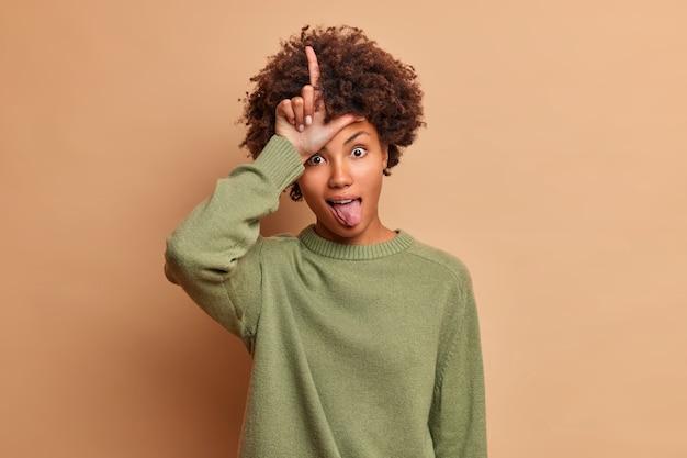 Jovem engraçada de cabelo encaracolado faz gesto de perdedor mostra a língua vestida com um macacão casual isolado sobre uma parede marrom zombando de alguém que perdeu a aposta