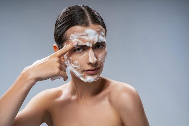 Jovem engraçada lavando o rosto com espuma